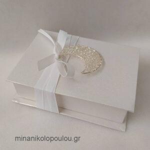Κωδ. Β-103 Μπομπονιέρα Γάμου Κουτάκι (10x14x4εκ) με μισοφέγγαρο μεταλλικό (4εκ), 5 κουφέτα, δεμένη με κορδέλα χρυσή (0,6εκ). Χρώματα κουτιού: εκρού, λευκό. Για 50-150 τεμ. 2,80 €/τεμ. Χωρίς διακοσμητικό 2,30 €/τεμ.
